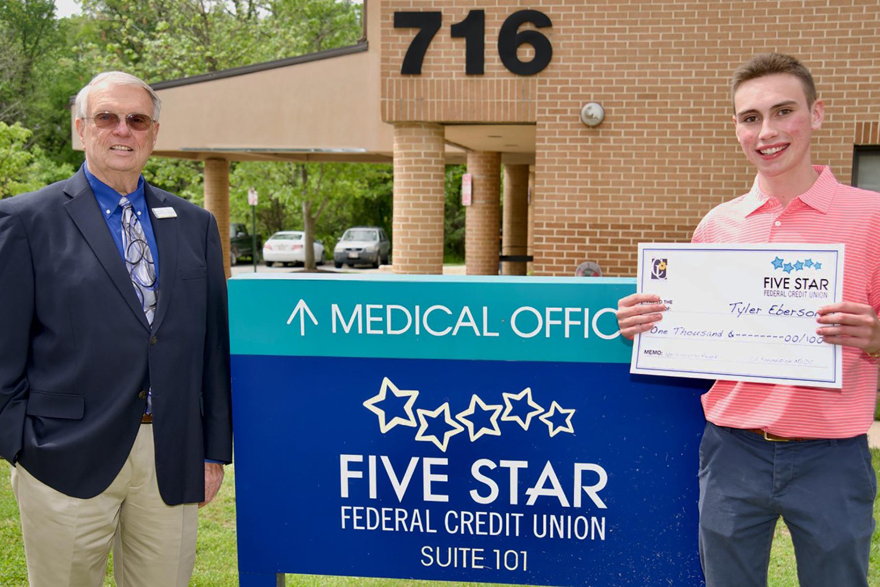 Paul Coakley presents a CU Foundation scholarship check to Tyler Ebersole.