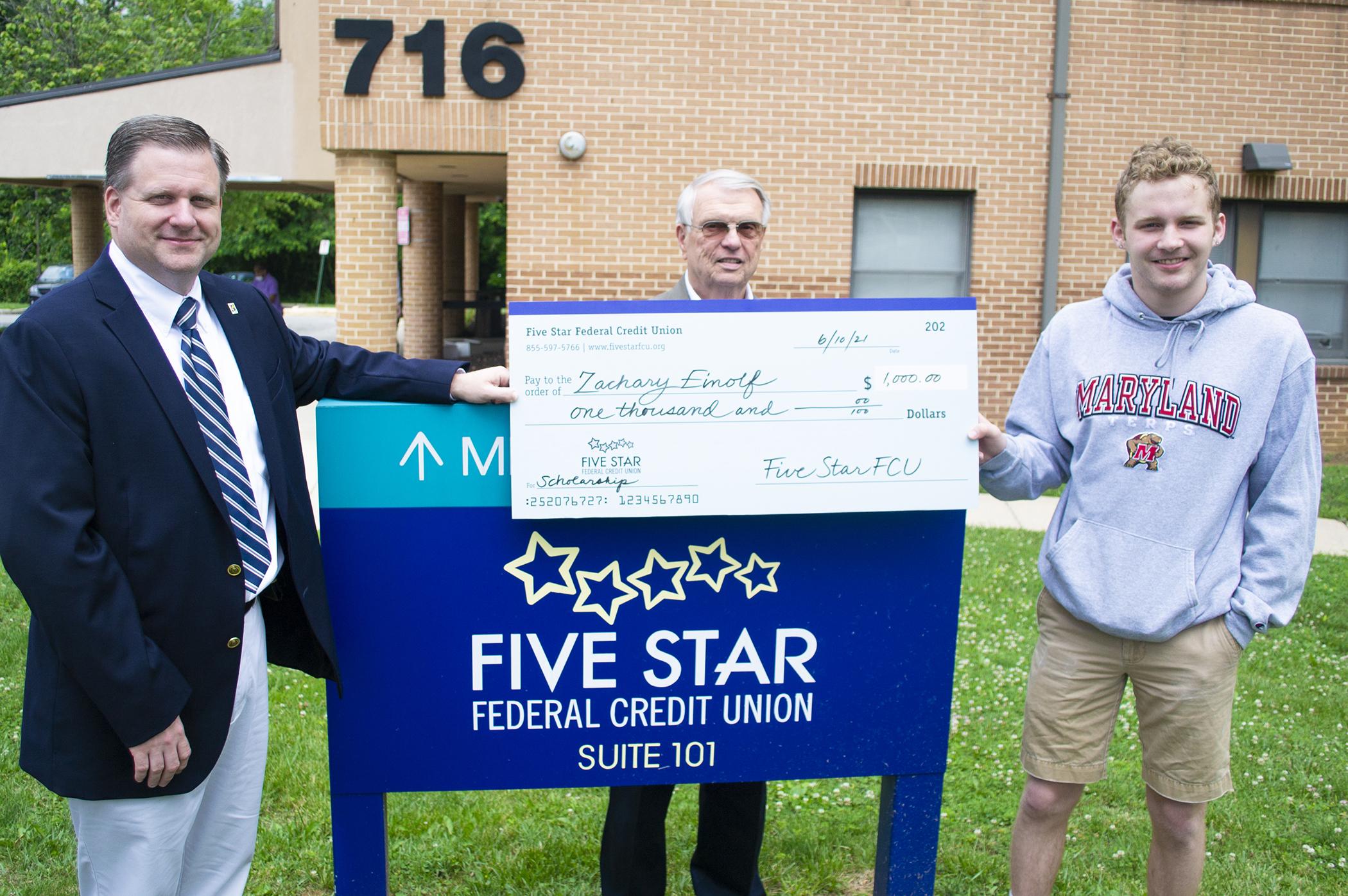 Jim Whipp and Paul Coakley present scholarship check to Zachary Einolf.